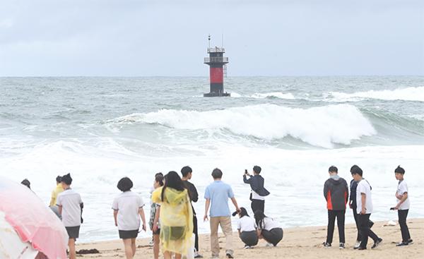 6일 개장한 강릉 경포해수욕장을 찾은 관광객들이 20도의 낮은 온도와 비바람으로 인한 높은 파도 앞에서 아쉬워하고 있다.