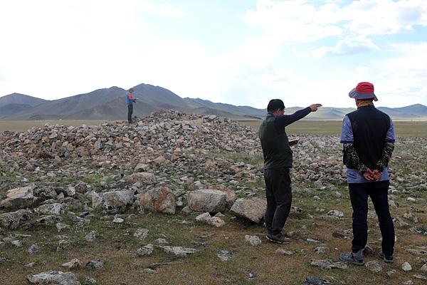 비석 앞에 만들어진 적석총 규모를 측량하고 있는 답사단원들. 중앙부분이 움푹패여 발굴이나 도굴이 이뤄졌던 흔적이 보였다