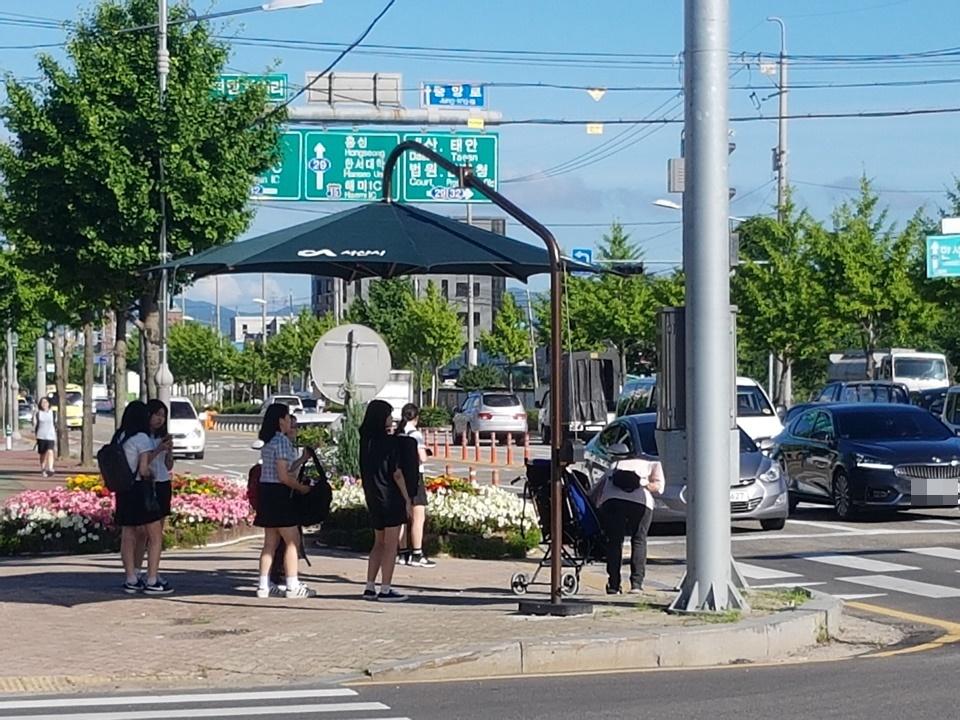폭염이 계속되자 시민들과 하교길 학생들은 신호를 기다리면서 횡단보도에 마련된 그늘막에서 잠시 쉬어가기도 한다.