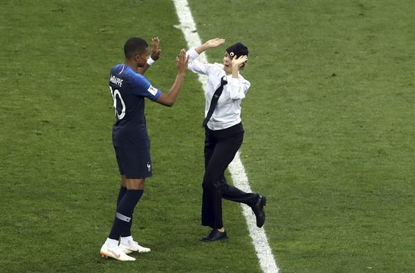 2018년 7월 16일 오전 0시(한국시간) 열린 러시아 월드컵 결승전 프랑스와 크로아티아의 경기. 경기 도중 난입한 여성이 프랑스의 음바페에게 접근하고 있다.
