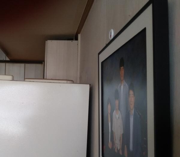 기자의 집 벽에 걸려 있는 가족사진. 무료사진 믿고 갔다가 30만원을 지불했다
