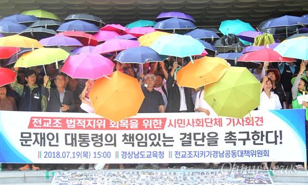 """'전교조 지키기 경남공동대책위원회'는 7월 19일 오후 경남도교육청 현관에서 """"전교조 법적지위 회복을 위한 문재인 대통령의 책임있는 결단을 촉구한다""""는 제목으로 기자회견을 연 뒤, 전교조와 함께 비를 맞는다는 생각으로 우산을 썼다."""