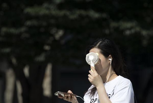 폭염이 이어지고 있는 17일 오전 서울 세종로사거리에서 한 시민이 휴대용 선풍기로 더위를 식히고 있다.