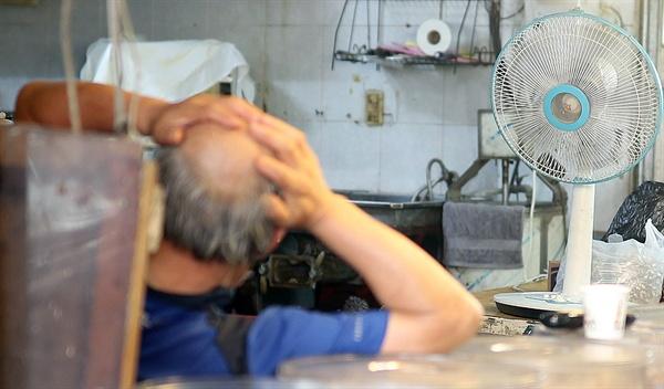 폭염 경보가 발령된 16일 오후 밀양시 내일동 전통시장에서 한 상인이 선풍기 앞에서 더위를 식히고 있다.