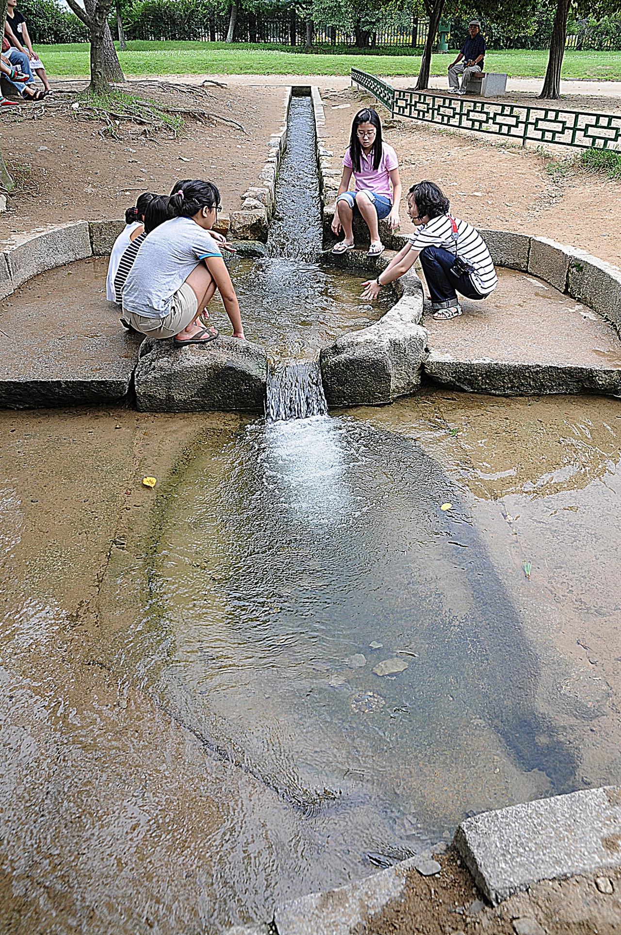 월지 입수구 월지로 물이 들어오는 입수구를 복원해놓았다. 사람들은 물에 손을 넣고 피서 즐기기에 바쁘다.