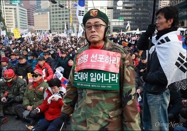 2016년 12월 31일 오후 서울 덕수궁 대한문앞에서 열린 탄기국(대통령탄핵기각을 위한 국민총궐기운동본부) 주최 집회에서 군복을 입은 참가자가 '계엄령을 선포하라' '군대여 일어나라'가 적힌 손피켓을 몸에 붙이고 있다.