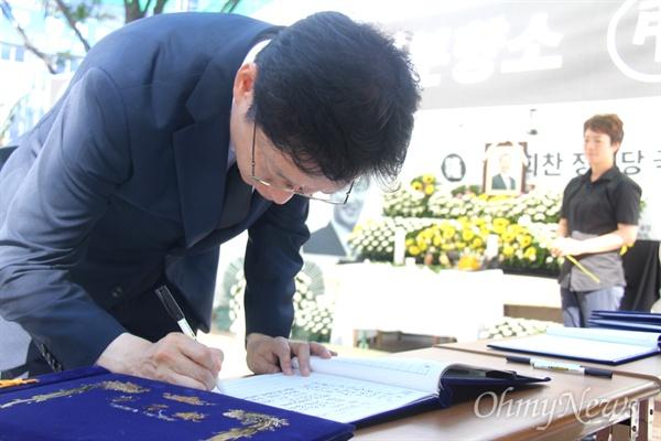 김경수 경남도지사가 7월 24일 아침 창원 중앙동 한서병원 앞 문화광장에 마련된 '고 노회찬 국회의원 시민합동분향소'를 찾아 조문에 앞서 방명록에 서명하고 있다.