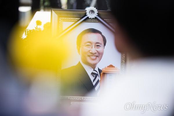 27일 오후 경기도 남양주 마석모란공원에서 진행된 고 노회찬 의원의 하관식에서 추모객 사이로 영정이 보이고 있다.