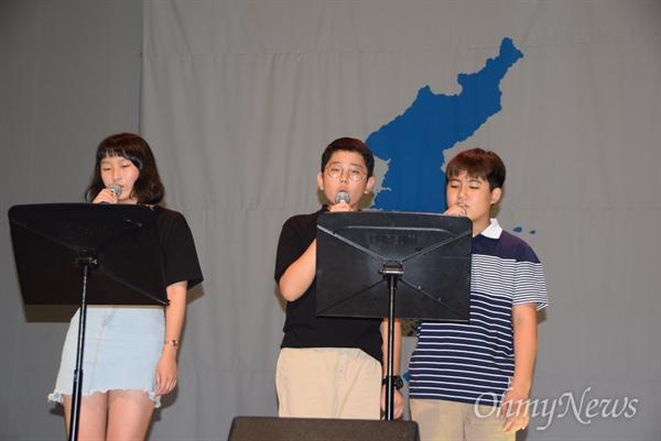"""경남평화회의는 7월 27일 저녁 창원 늘푸른전당에서 """"평화와 통일을 노래하다""""는 제목으로 '7.27 65주년 평화콘서트'를 열었고, 학생들이 '둘이서 통일 노랫말 짓기' 입상작을 노래하고 있다."""