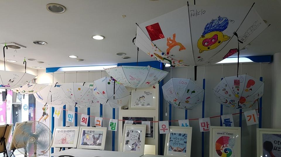 최근 '맹꽁이 도서관'은 서산시 번영로에서 아이들을 대상으로 색다른 체험을 하고 있다. 아이들이 읽은 그림 동화를 우산에 직접 그려 넣고 있다. 우산 하나하나를 살펴볼 때마다 동화책 한 권을 다 읽은 느낌이다. 우산에 그림을 그리는 아이들의 모습이 사뭇 진지하고 신중하다.