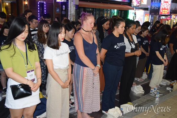"""'일본군 위안부 역사의 과제를 위한 국제청소년대회'에 참석한 5개 나라 고등학생과 대학생들이 8월 1일 저녁 창원마산 오동동 인권자주평화다짐비 앞에서 """"일본군위안부 피해자 기림일 기념 추모문화제""""를 열었다. 참가자들이 묵념을 하고 있는 모습."""