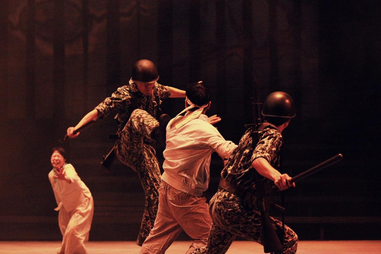 망월할매의 아들이 계엄군에 의해 죽임을 당한다. 13년 만에 우금치 극단이 서울 대학로 예술극장에서 2주간 2편의 마당극 공연을 하게 되었다. 사진은 '천강에 뜬 달'의 한 장면으로 5.18광주민주화항쟁 당시 망월할매의 아들이 계엄군에 의해 폭행당하며 끌려가는 장면이다.