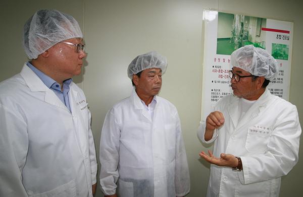 이완영 의원(가운데)이 꽃벵이 등을 활용한 건강기능식품을 만들고 있는 한미양행 생산 공장을 방문해 제품 생산 과정에 대해 설명을 듣고 있다.
