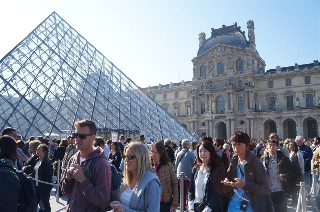 루브르 박물관 입장을 위해 유리 피라미드 앞에 줄을 선 관람객들