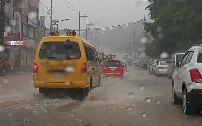6일 오전 10시 경, 강원 강릉 강일여고 앞 도로에 집중호우로 빗물이 넘쳐 차량이 거북이 운행을하고 있는 모습. 강릉지역은 지난밤부터 쏟아지기 시작한 집중호우로 도로침수 등 피해가 발생해 전 지역에 교통 통제를 실시하고 있다.