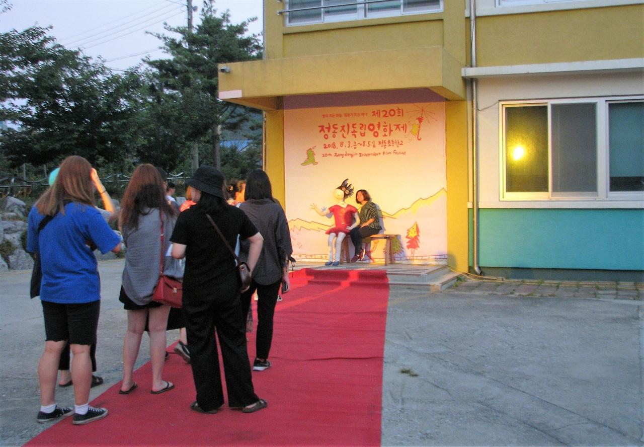 레드카펫으로 입장한 관객들이 정동진독립영화제의 상징 우산살소녀 앞에서 기념사진을 찍고 있다.