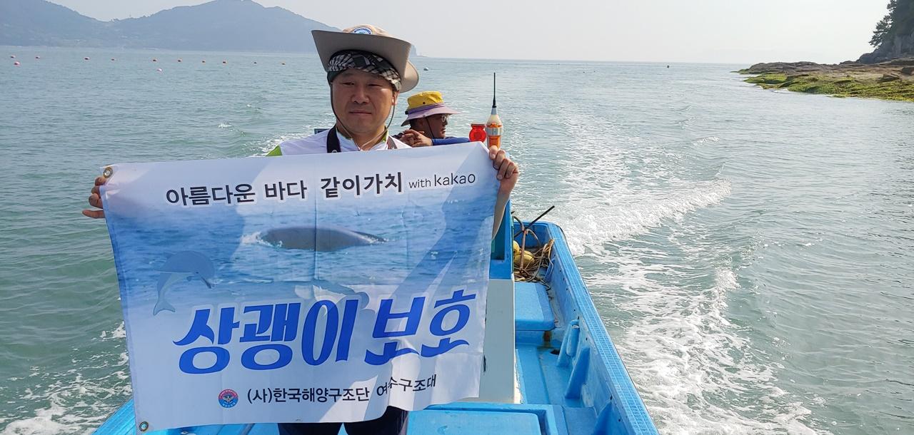 한국해양구조협회 여수구조대 박근호 대장이 상쾡이가 가장 많이 출몰하는 자신의 고향인 월호도 앞에서 현수막을 펼친 모습