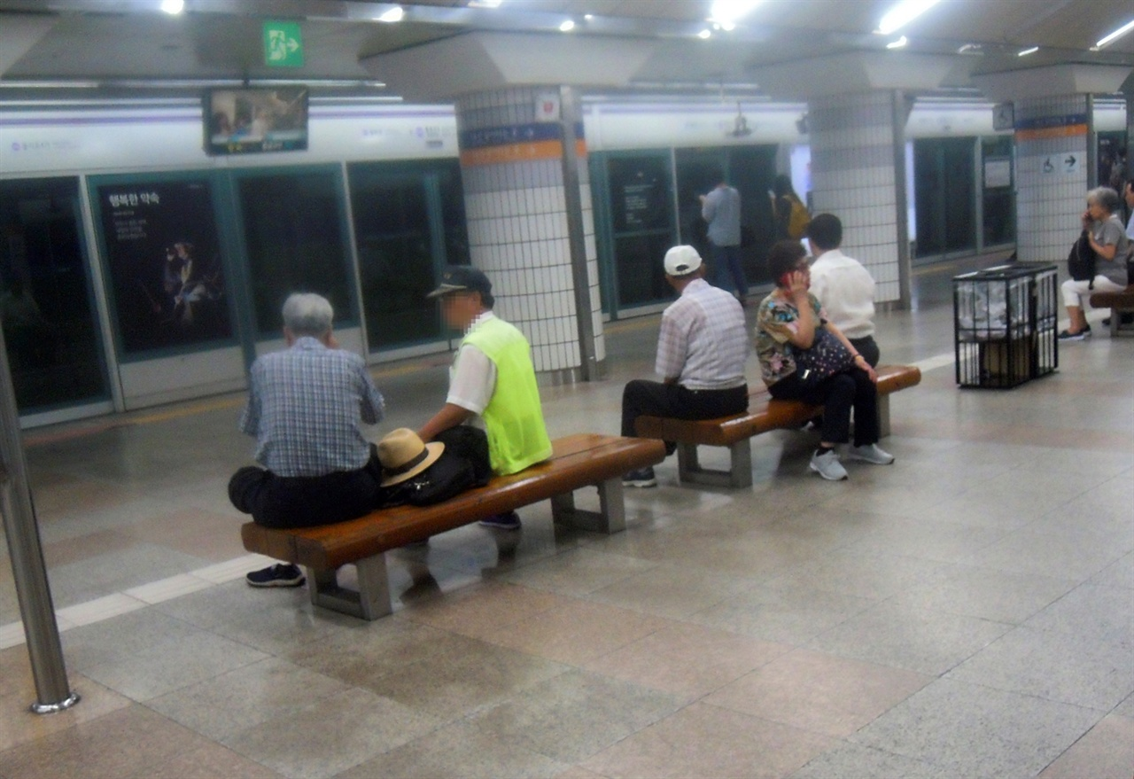 지하철 승강장에서 쉬고 있는 노인들