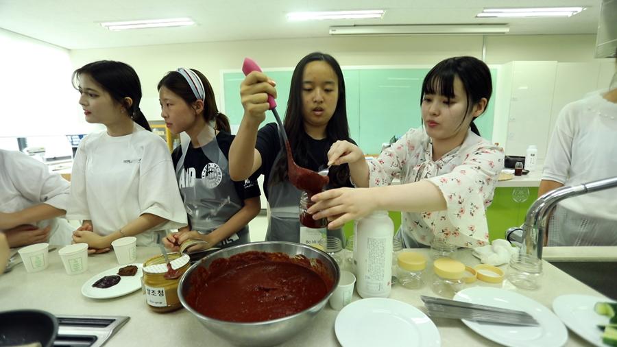 전통 고추장 만들기 수업 학생들이 직접 만든 전통고추장을 용기에 담고 있다.