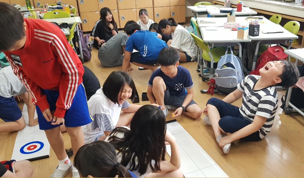 미세먼지가 심하던 날, 체육시간 교실에서 학생들이 컬링게임을 즐기고 있다.