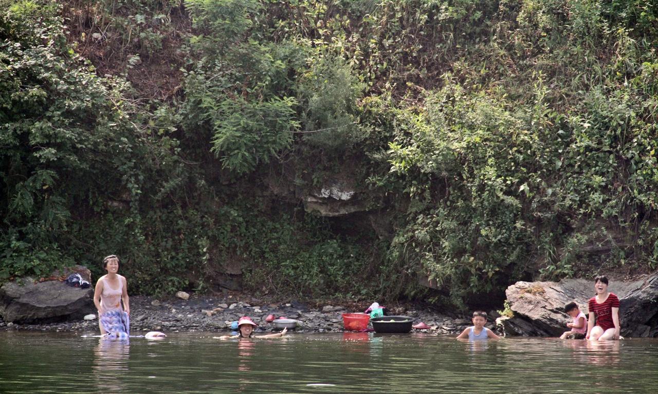 물놀이 나온 가족 이모일까 고모일까 어린아이 둘이 포함된 일가족이 압록강에서 피서를 즐기고 있다. 오른쪽 끝 붉은 옷을 입은 사람이 활짝 웃어 보이고 있다. 이들은 우리들을 향해 손을 흔들어 주기도 하였다.