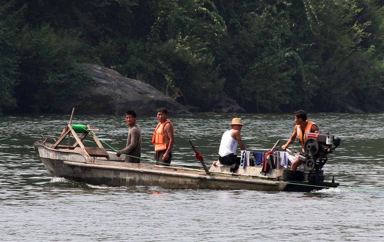 압록강의 북한 어부들 압록강에서 그물을 쳐놓고 배를 이용하여 물고기를 잡는 북한 어부들. 경운기에서 사용하는 엔진을 동력으로 이용하고 있는 점이 이채롭다.
