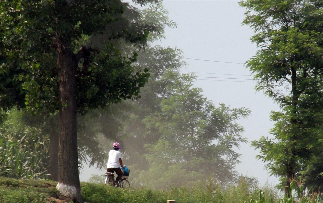 자전거 일상 트럭이 지나가고 먼지가 자욱한 압록강변 길을 한 여인이 자전거를 타고 가고 있다.