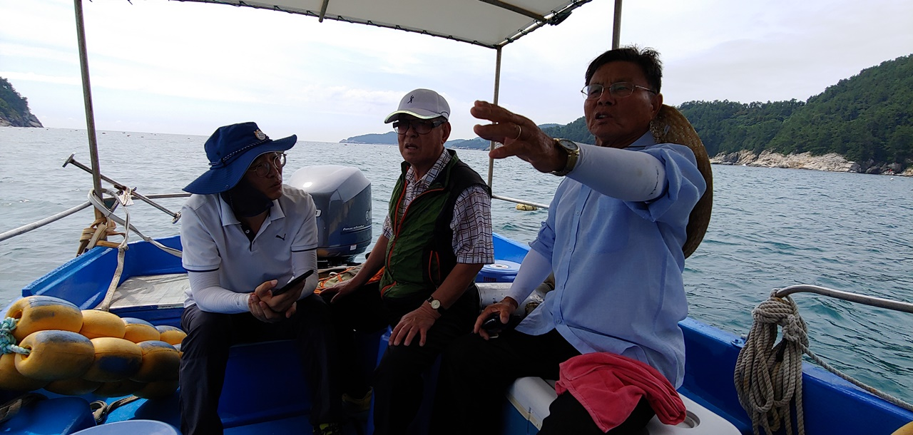 이야포 미군폭격 사건 생존자인 이춘혁씨와 주철희 박사에게 목격자인 마을주민 이사연씨에게 당시 피난선 침몰현장을 가르키고 있다