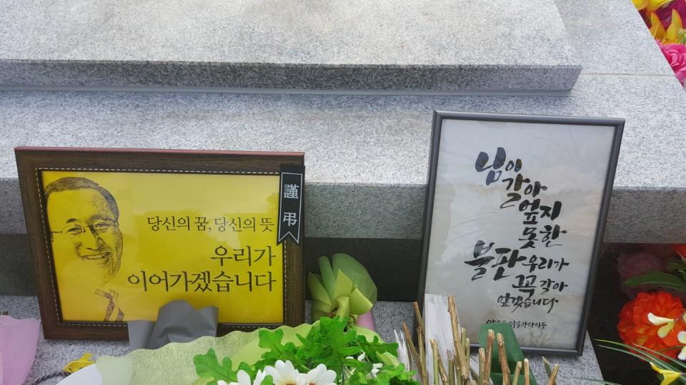 묘소 앞에 놓인 액자에 '님이 갈아엎지 못한 불판, 우리가 꼭 갈아엎겠습니다'라는 추모 글이 쓰여 있다.