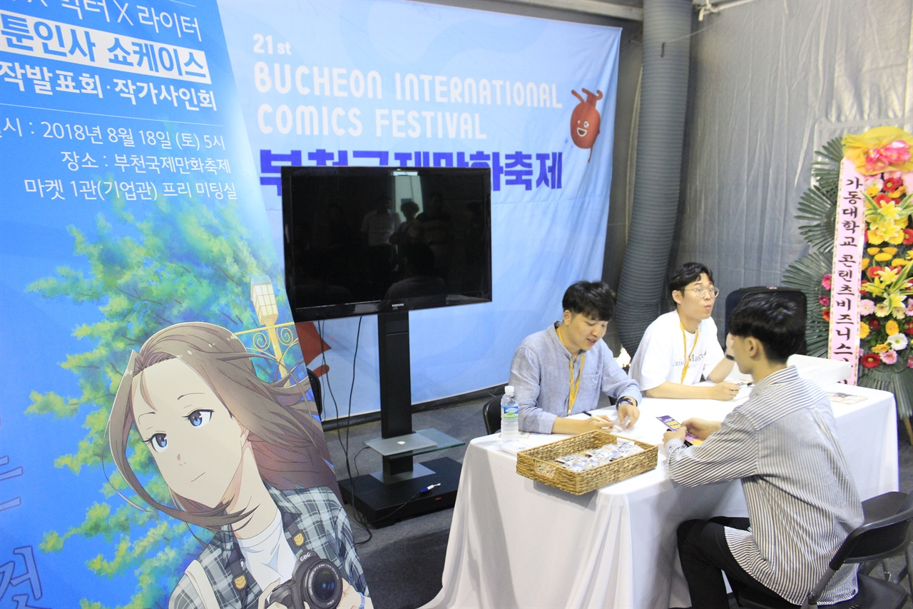2018 부천국제만화축제에서는 새로운 웹툰 쇼케이스와 함께 사인회가 열렸다. <고양이에게 보이는 것>의 작가 빅터(왼쪽)와 낙타(오른쪽)가 사인하고 있다.