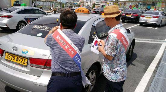택시에 조기들 달고 있는 독립운동정신계승사업회 회원들