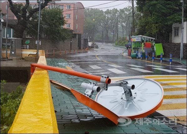 교차로에 설치된 원형 거울이 강한 바람에 휘었다.