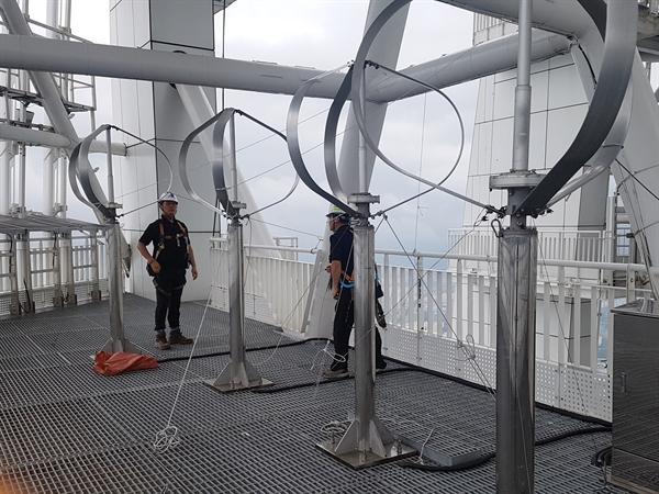 롯데월드타워 최상층부 랜턴구간에 설치된 풍력발전기에 작업자가 와이어 고정 작업을 하고있다.