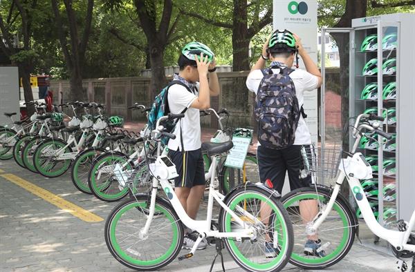 7월 20일 오후 서울 여의도 지하철5호선 여의나루역 1번 출구 앞 따릉이 대여소에서 청소년들이 공공자전거 따릉이를 대여하며 안전모를 써보고 있다.