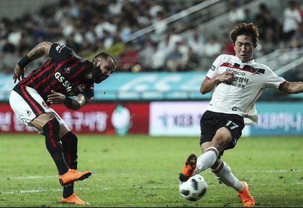 슛 하는 에반드로, 막는 강상우 22일 오후 서울월드컵경기장에서 열린 FC서울 대 포항 스틸러스 경기. 서울 에반드로가 슛을 하자 포항 강상우가 몸을 날려 공을 막고 있다.