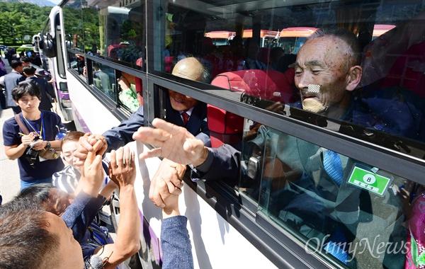2박3일간의 상봉행사를 마친 북측 이산가족이 26일 금강산 호텔에서 북측으로 향하는 버스에 탑승한 후 눈물을 훔치며 작별 인사를 하고 있다.