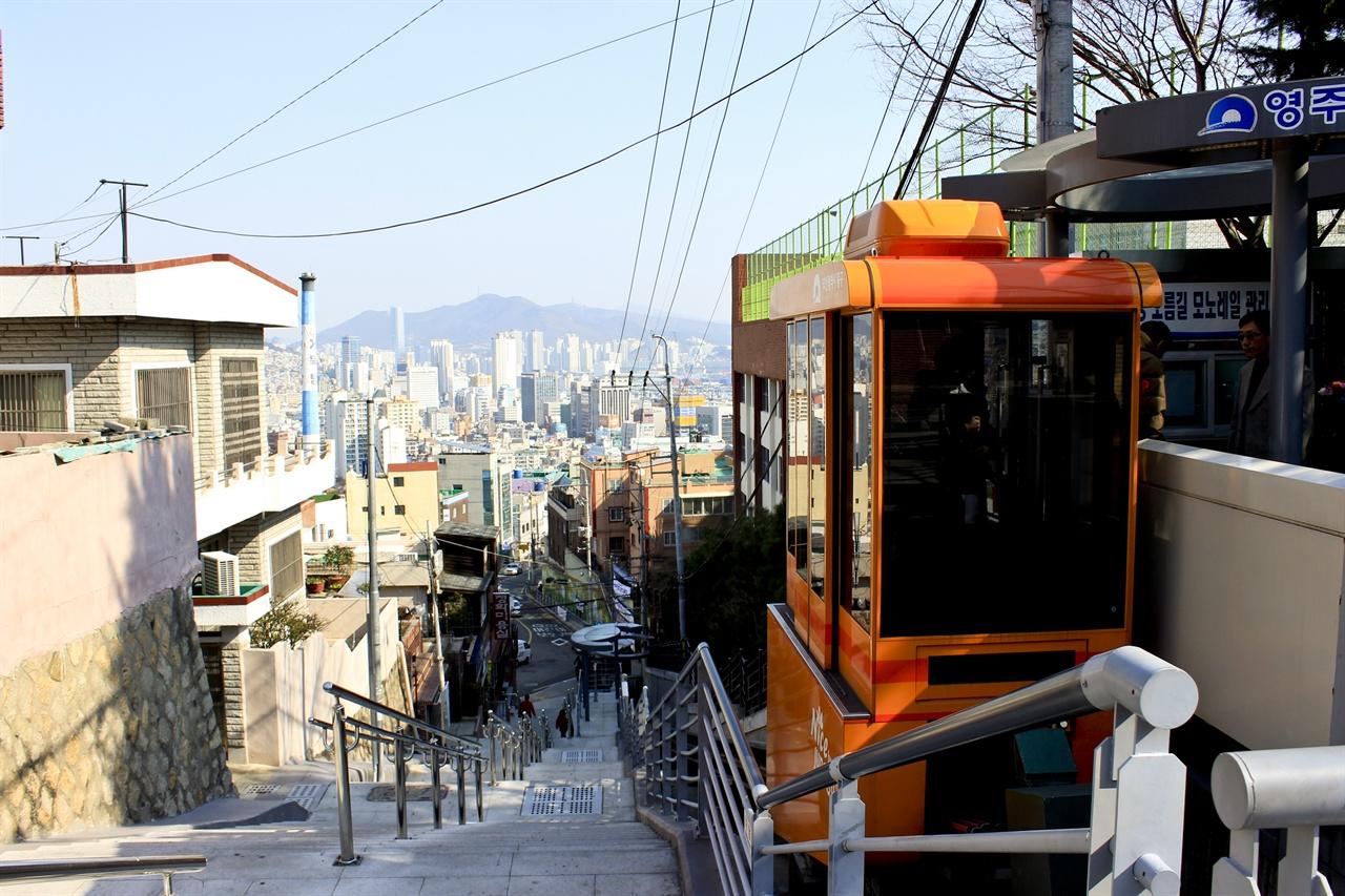 2014년부터 부산 중구 영주동 주민들의 발이 되어주고 있는 부산 영주동 모노레일이 승객을 싣고 있다. 모노레일 뒤로 부산 시가지의 풍경이 보인다.
