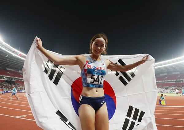 정혜림 태극기 세리머니 26일(현지시간) 인도네시아 자카르타 겔로라 붕 카르노(GBK) 주경기장에서 열린 여자 100m 허들 결승전.  한국 정혜림이 1위로 결승선을 통과한 뒤 태극기 세리머니를 하고 있다.