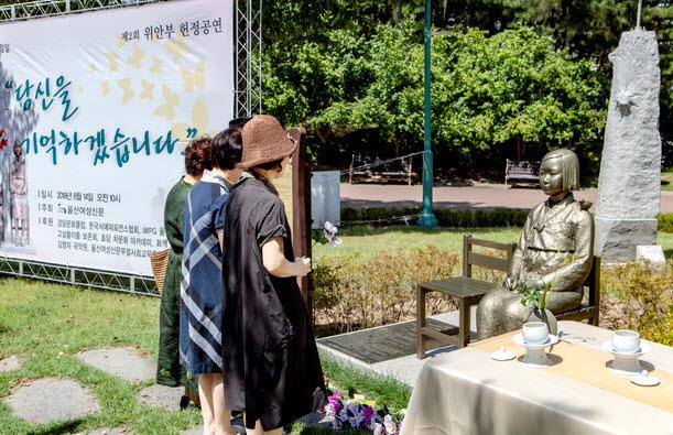 8월 14일 울산 남구 신정동 울산대공원 동문 광장 입구에 있는 '평화의 소녀상'앞에서 열린 위안부 기림 행사에서 참석자들이 헌화하고 있다