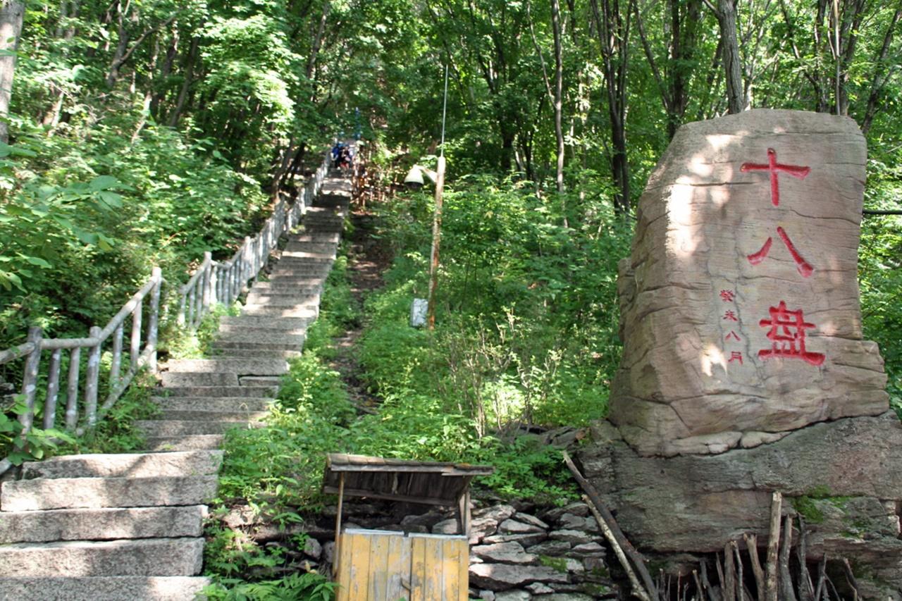 오녀산성으로 오르는 길  오녀산은 해발 800미터이다. 산에 오르는 계단 옆으로 십팔판이라는 길이 있는데 고구려시대에는 말과 마차도 산성에 오를 수 있도록 18번을 굽이굽이 돌아 오르게 만들었다고 한다. 지금은 천여 개의 계단이 오르는 길을 대신하고 있다.