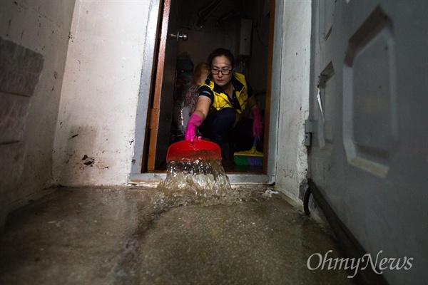 응암초 녹색어머니회 회원이 자원봉사로 응암동 수해 피해자 세대를 찾아 고여 있는 물을 퍼내고 있다.
