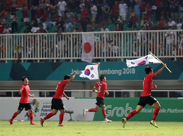 일본 꺽고 아시안게임 우승 1일 오후(현지시간) 인도네시아 자와바랏주 보고르 치비농의 파칸사리 스타디움에서 열린 2018 자카르타·팔렘방 아시안게임 남자축구 결승전 한국과 일본의 경기가 한국의 2대1 승리로 끝났다. 손흥민과 선수들이 경기 종료 휘슬이 울리자 태극기를 들고 그라운드를 누비고 있다.