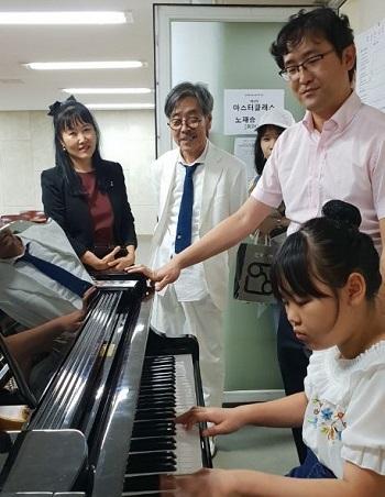 개인 레슨 공연이 끝나고 초등학생으로 보이는 한 어린이가 전문가 지도 하에 무료 피아노 레슨을 받고 있다.