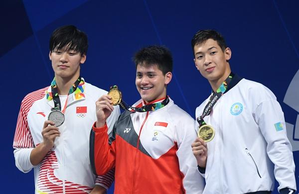2018년 8월 23일, 제18회 자카르타 아시안게임 남자 수영 50m에서 금메달을 딴 조셉 스쿨링(싱가포르)과, 은메달의 왕 펭(중국), 동메달의 아딜리벡 무신(카자흐스탄).