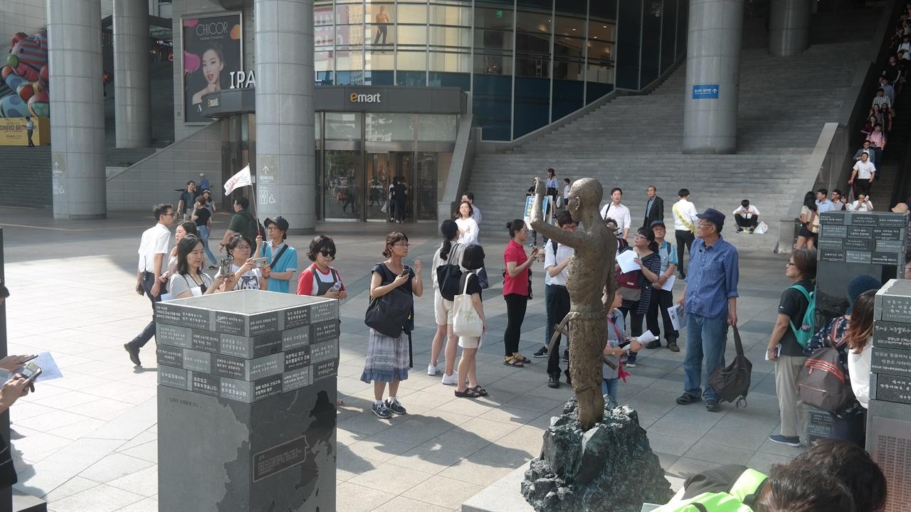 강제징용 노동자상 앞에서 설명을 듣고 있는 답사단원들의 모습