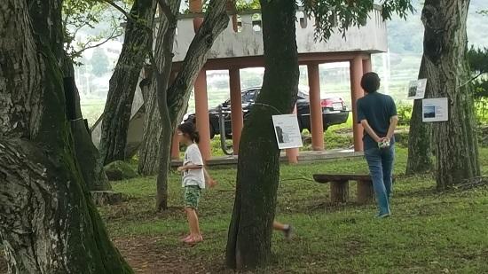 장산숲에서 고성국제디카시페스티벌은 끝났지만 디카시전시회가 계속 이어지는 가운데 관광객들이 작품을 감상하고 있다.