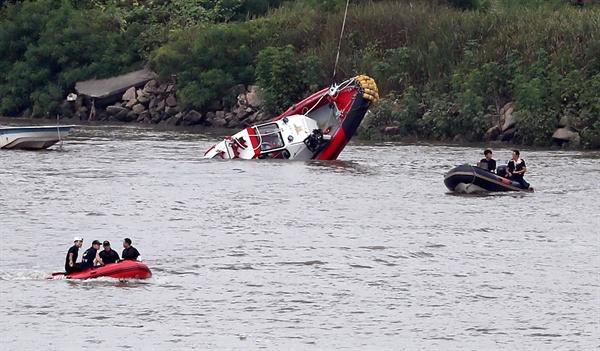 8월 13일 오후 경기도 김포시 고촌읍 신곡수중보 인근 강가에서 전복된 소방구조대 보트가 인양되고 있다.