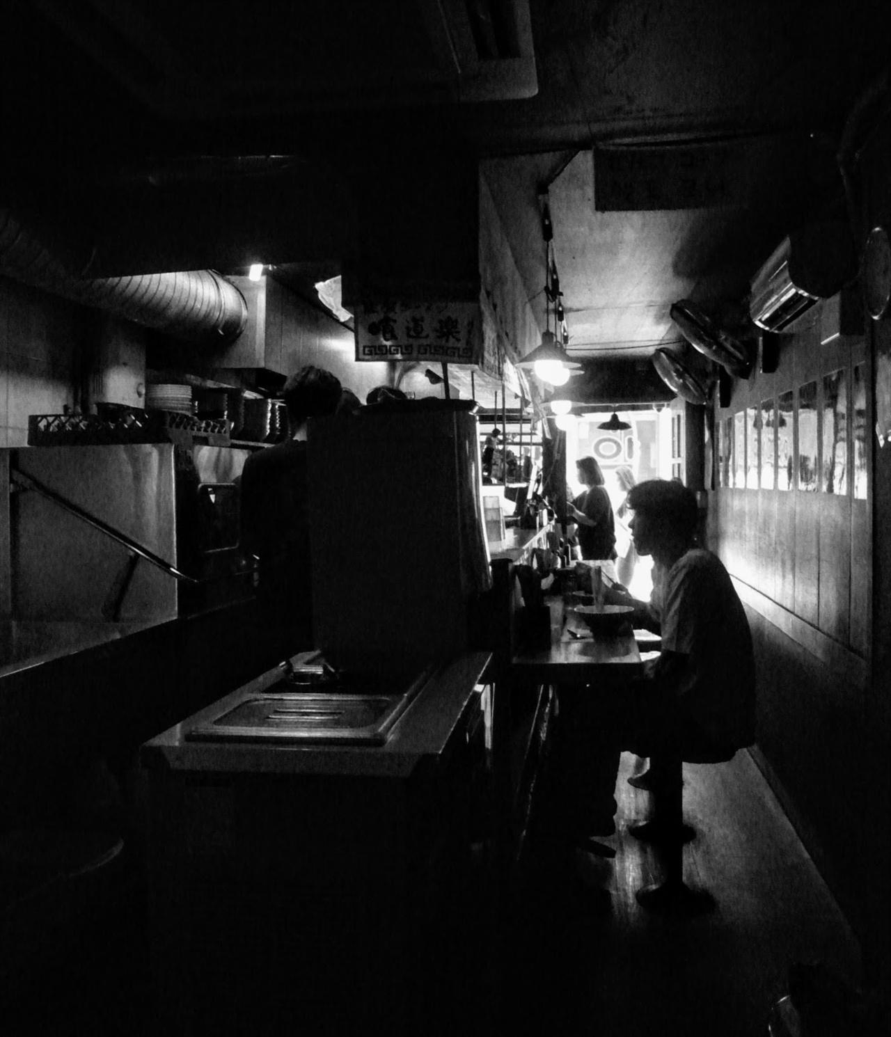 세장한 라면집 긴 테이블 앞에 손님이 앉아 라면을 먹고 있다. 가게가 매우 좁아서 등이 거의 벽에 붙는다