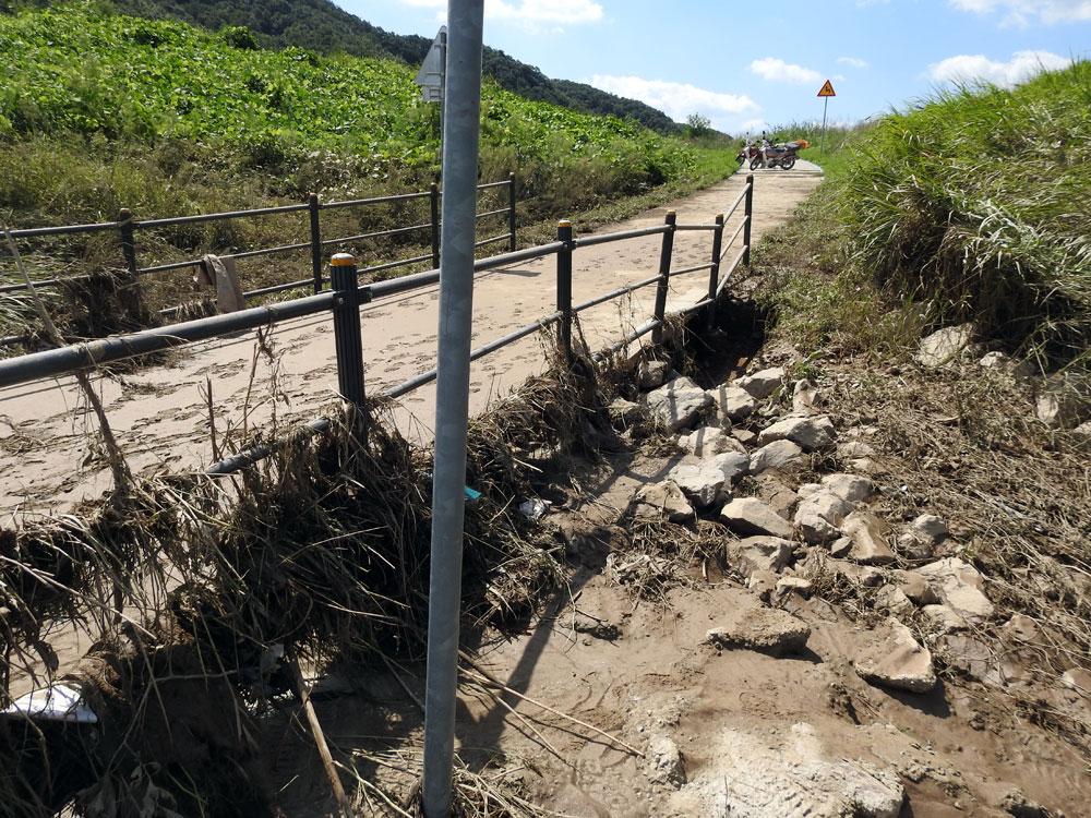 안전을 위해 설치한 펜스에는 각종 쓰레기가 걸리고 바윗덩어리가 유실되면서 시설물이 휘어져 버렸다.