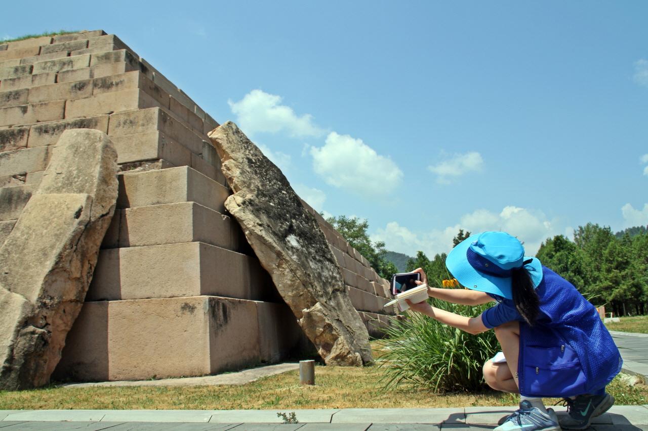 장수왕릉  기행단의 한 학생이 장수왕릉이 무너지지 않았던 이유라는 보고서를 작성하기 위하여 사진을 찍고 있다.